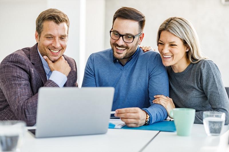 trzy osoby patrzące w kierunku laptopa